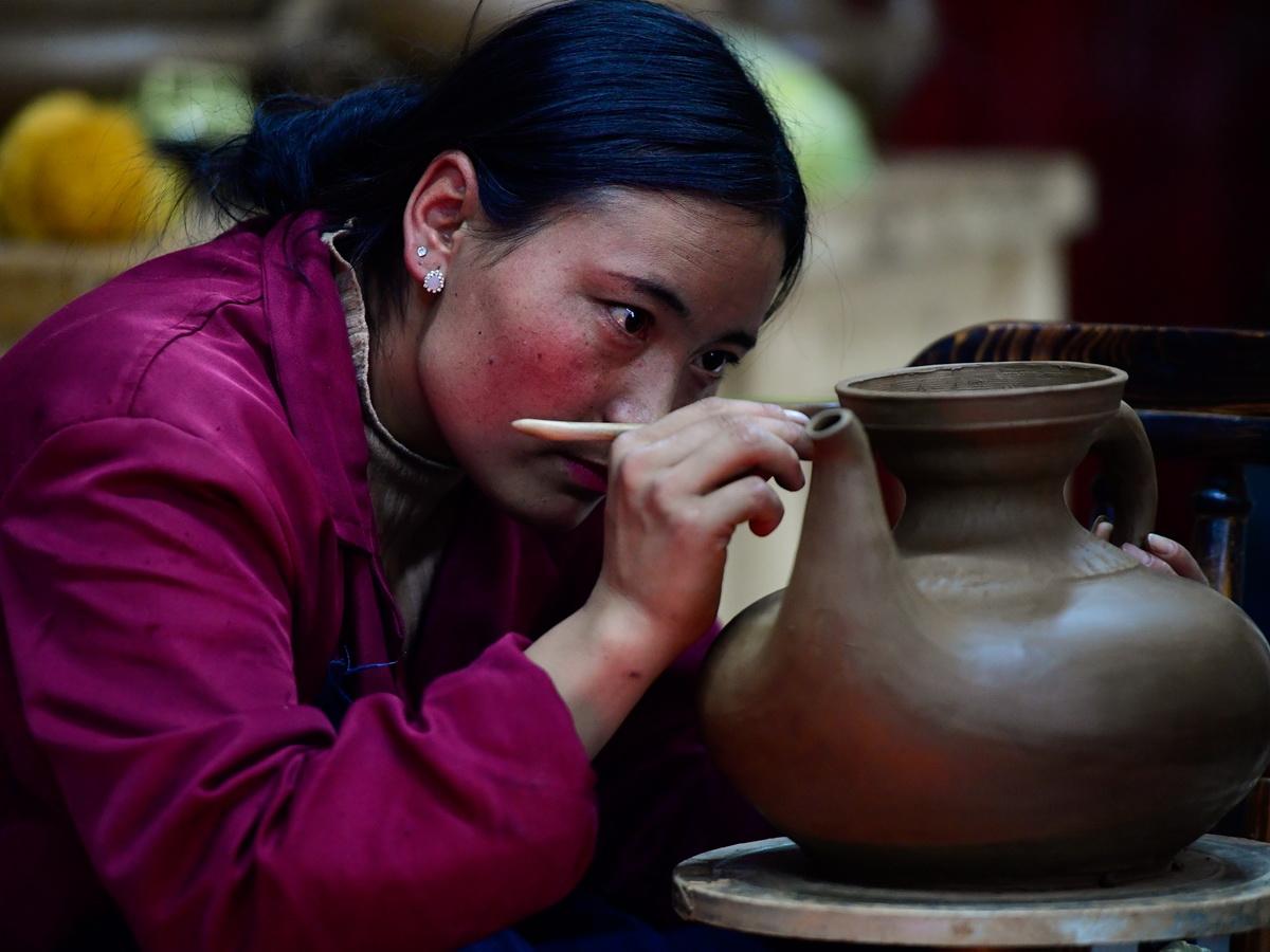 青海省果洛藏族自治州班玛县黑陶匠人闹吾措在制作传统藏式黑陶(2019年11月11日摄)。新华社记者 张龙 摄