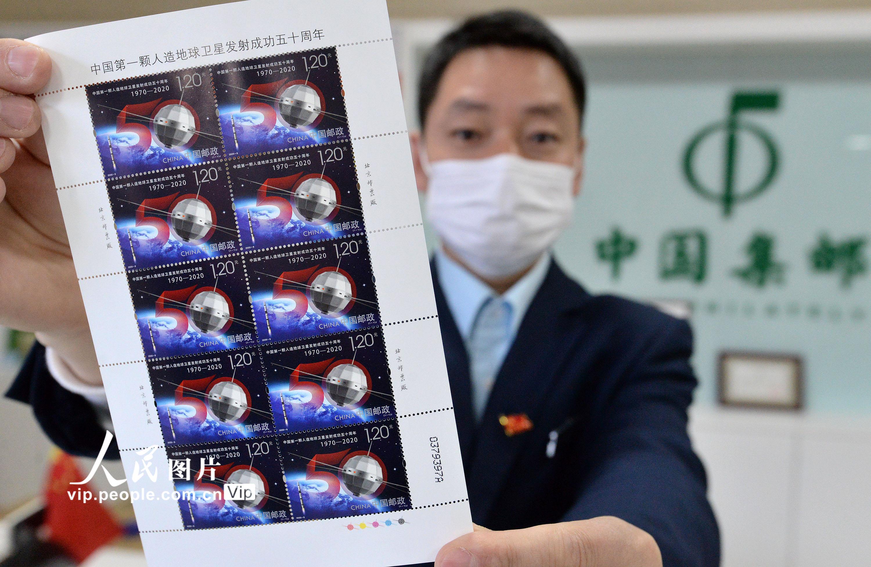 4月24日,中国邮政集团公司邯郸市分公司的工作人员展示《中国第一颗人造地球卫星发射成功五十周年》纪念邮票。