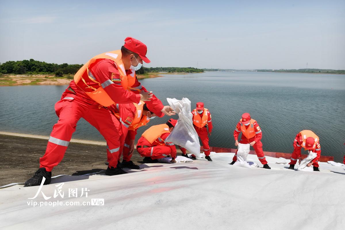"""4月25日,抢险救援人员在江西省高安市曾家桥水库演练现场采用土袋子堰、组合式防洪挡板和钢模子堤等构筑方法消除水库""""险情""""。"""