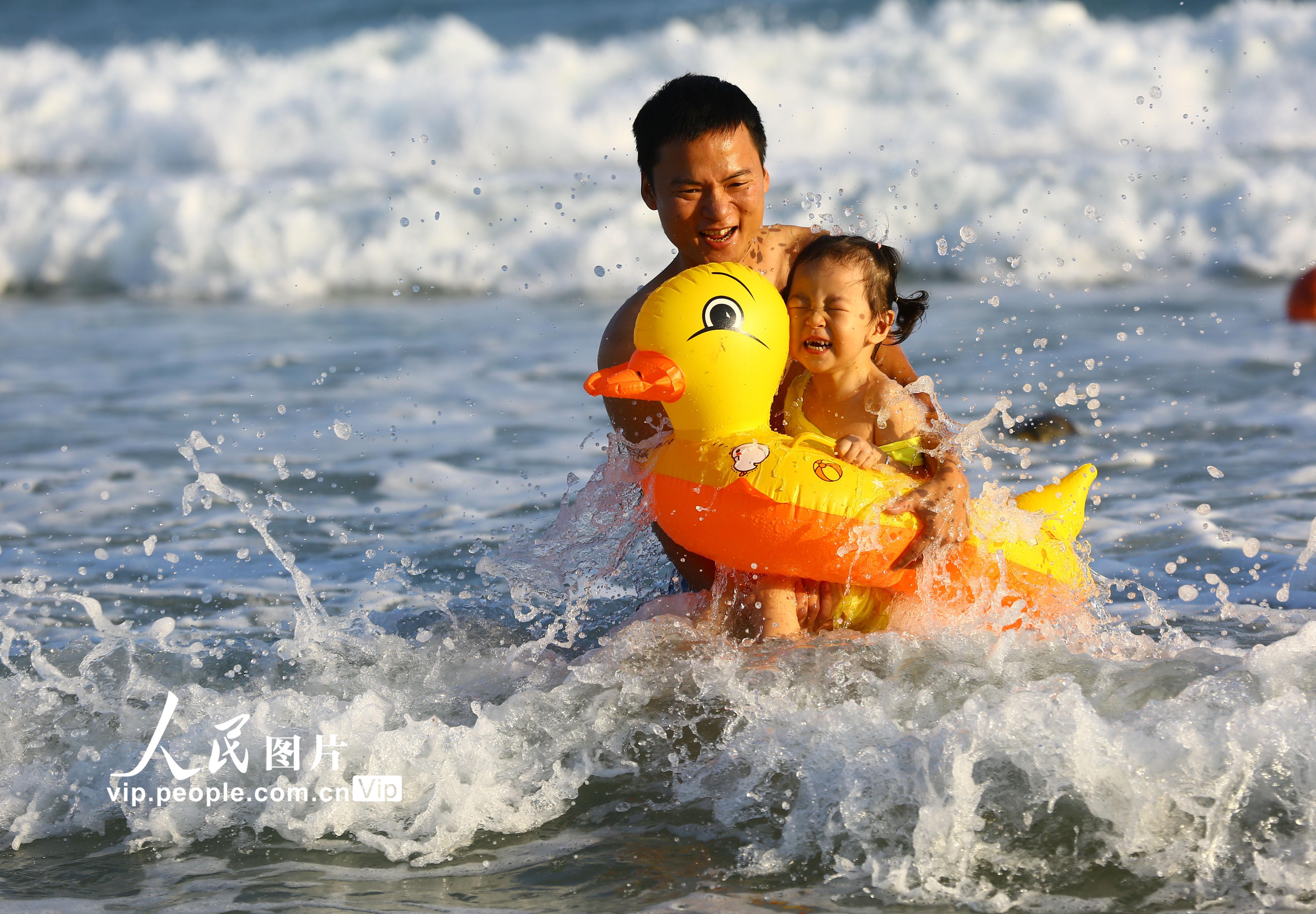海南三亚高温 游人海滨戏水消暑