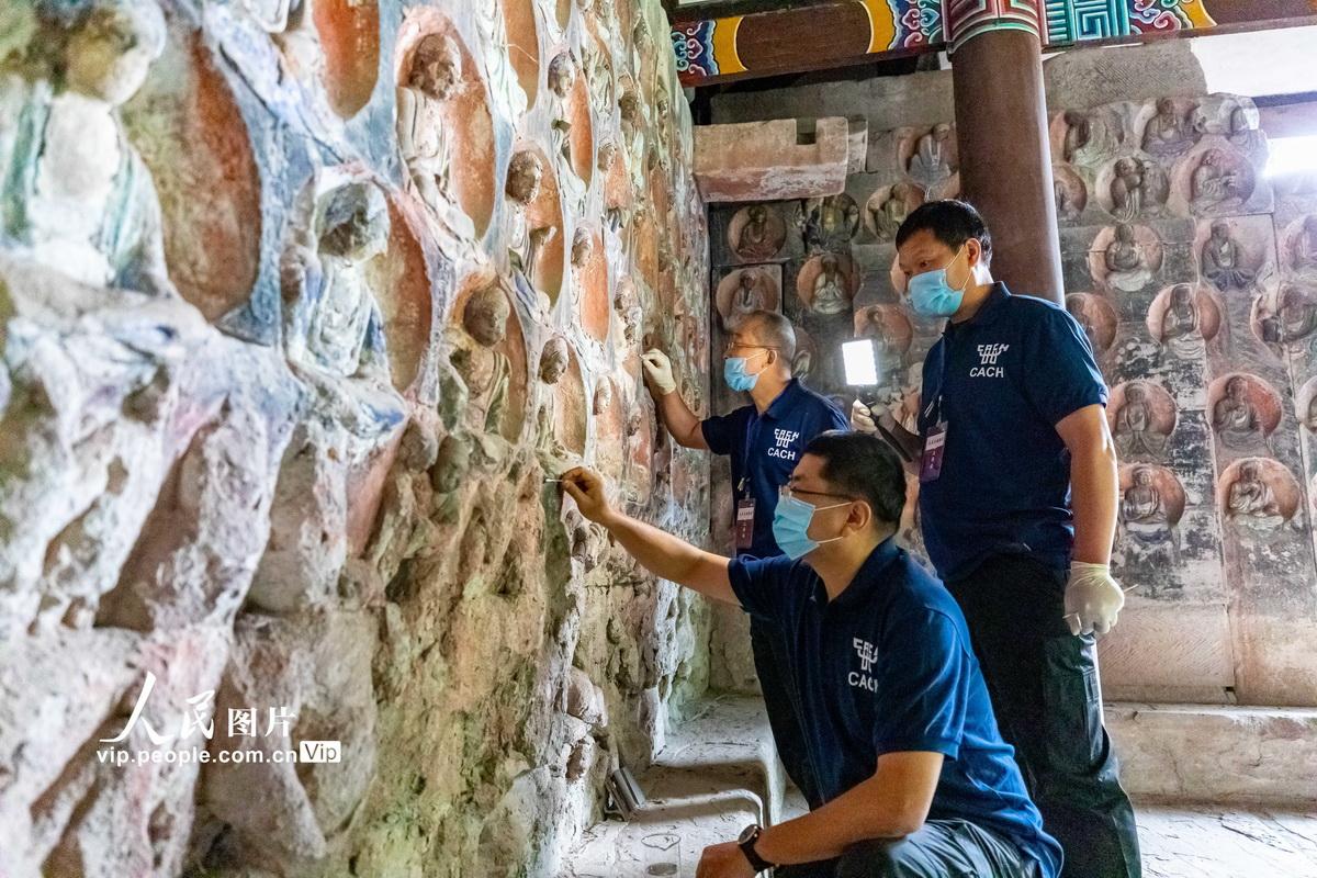 2020年5月9日,世界文化遗产重庆市大足石刻宝顶山小佛湾,修复专家对正在对摩崖造像进行清洁。