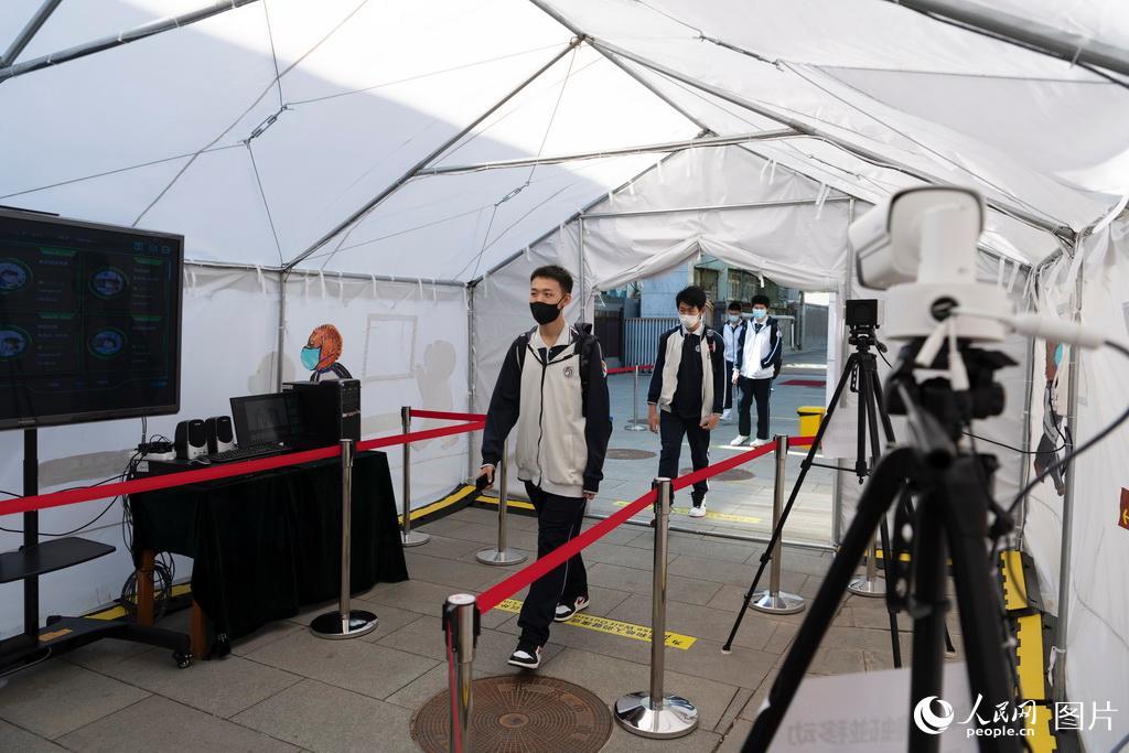5月11日,在北京市第一六六中学,学生通过测温棚后进入学校。(人民网记者 翁奇羽 摄) (2)
