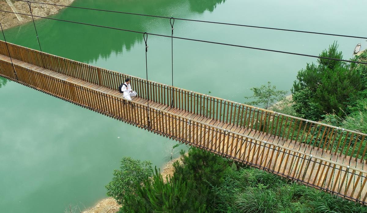 5月27日,出诊结束返程途中,村医龙光庆行走在双尧村的铁索桥上(无人机照片)。