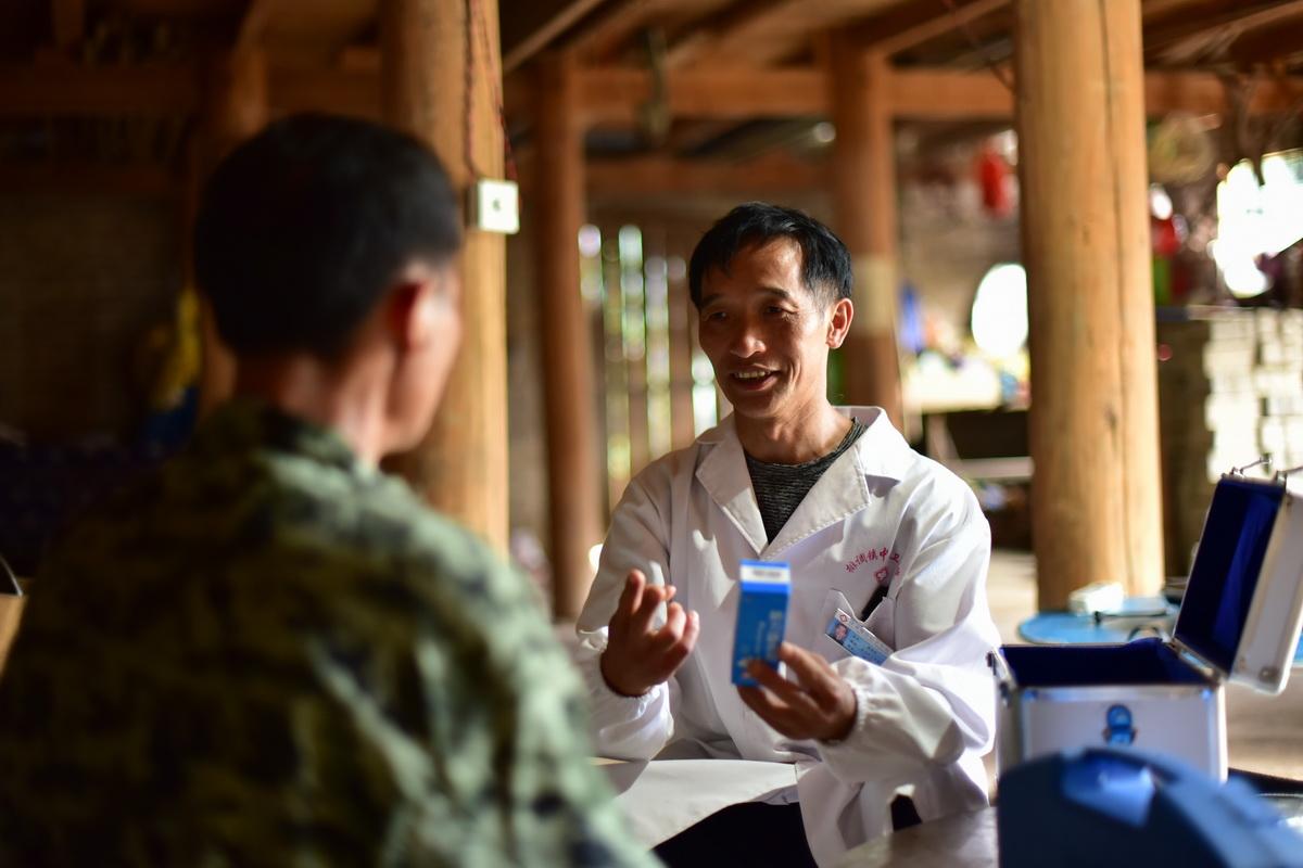 5月27日,村医龙光庆(右)向双尧村村民杨胜良介绍药品服用的注意事项。