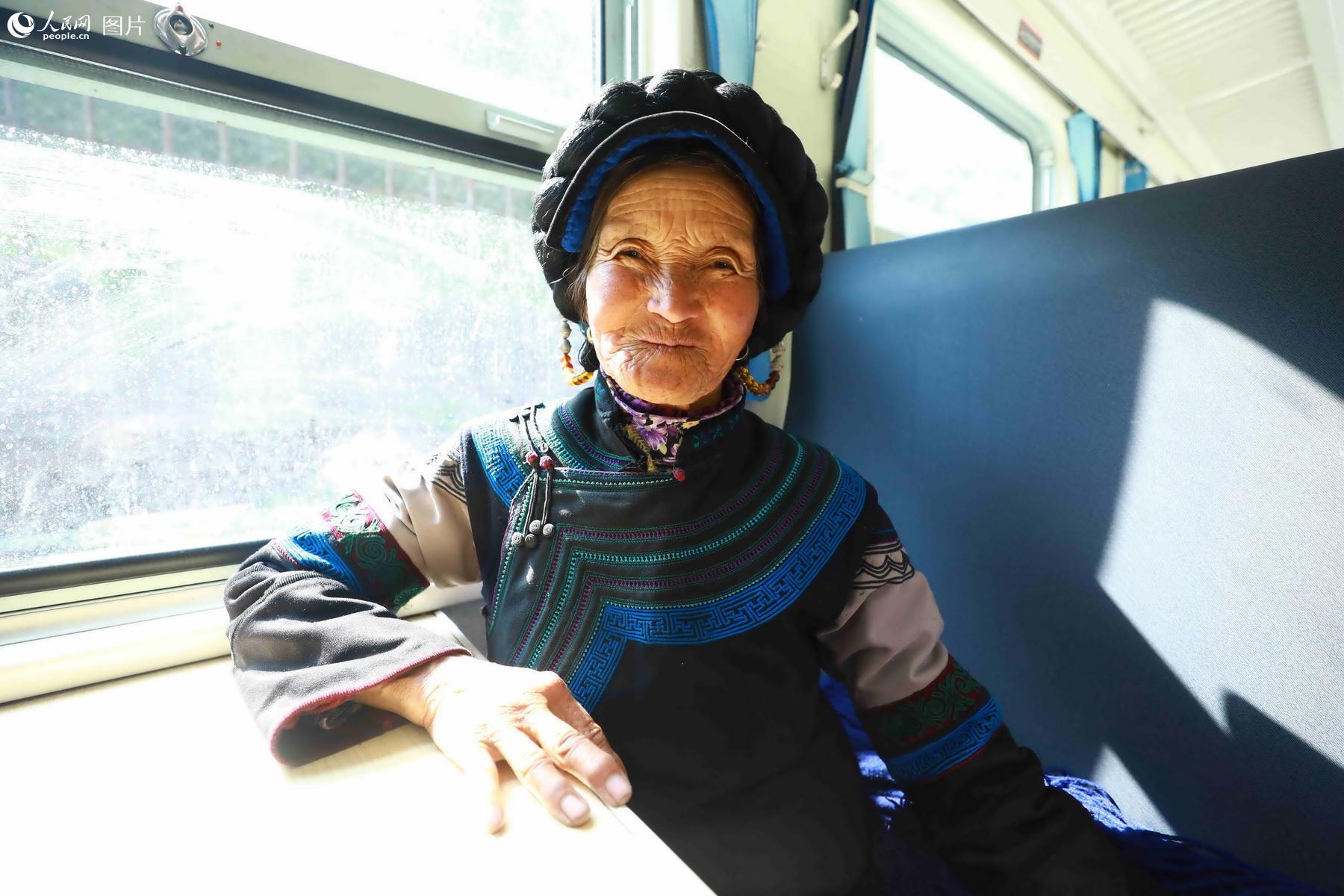5月20日,彝族老阿妈克迟支支莫,乘坐5619次列车前往普雄走访亲戚。(李锴 摄)