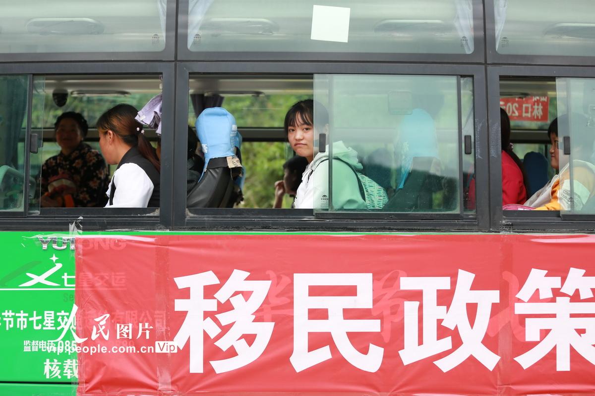 6月4日,葛雪和村民们在前往金海湖新区甘河街道幸福小镇易地扶贫搬迁集中安置点的车上。