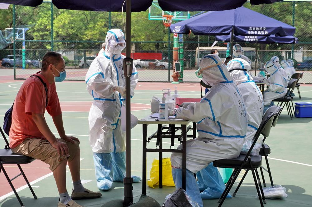 北京市丰台区东高地街道社区卫生服务中心的医护人员在高温下为居民进行采样(6月15日摄)。