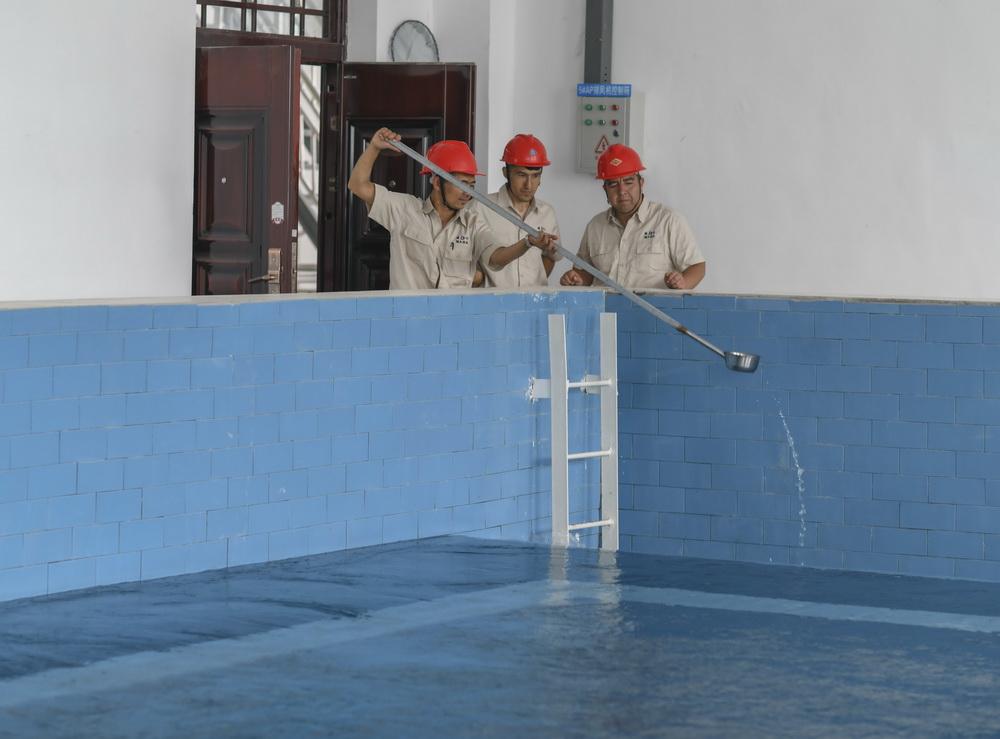 在新疆喀什地区城乡供水总水厂里,工作人员检查经过多次净化处理的安全水(6月8日摄)。这些安全水将通过近112公里的主管道直达伽师县,供应当地居民用水。新华社记者 赵戈 摄