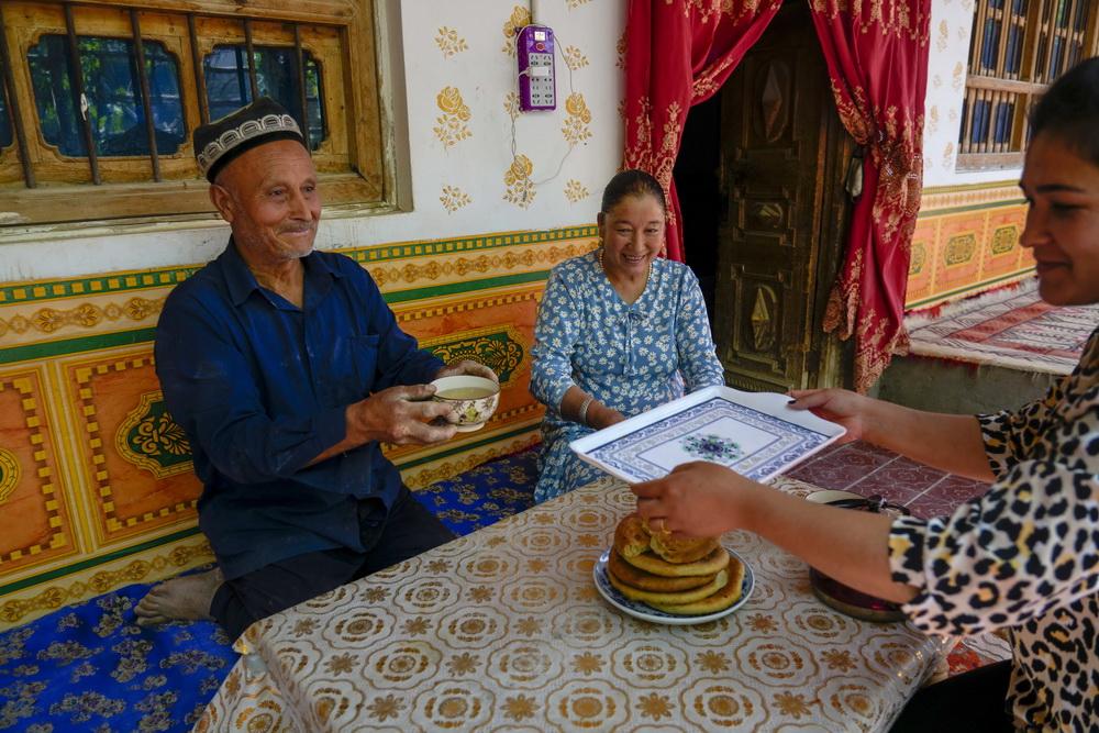 在新疆和田地区和田县布扎克村,68岁的艾比布拉·托合提(左)与家人一起休息喝茶(5月21日摄)。新华社记者 赵戈 摄