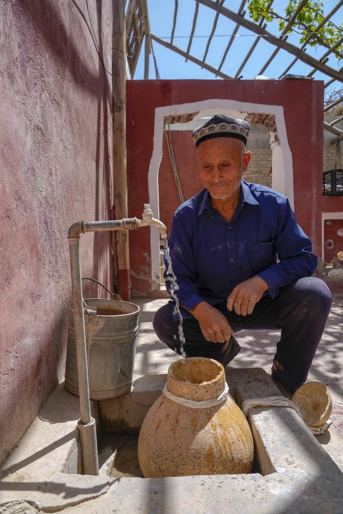 在新疆和田地区和田县布扎克村,68岁的艾比布拉·托合提在用葫芦接水(5月21日摄)。葫芦是南疆乡村常见的取水容器。新华社记者 赵戈 摄