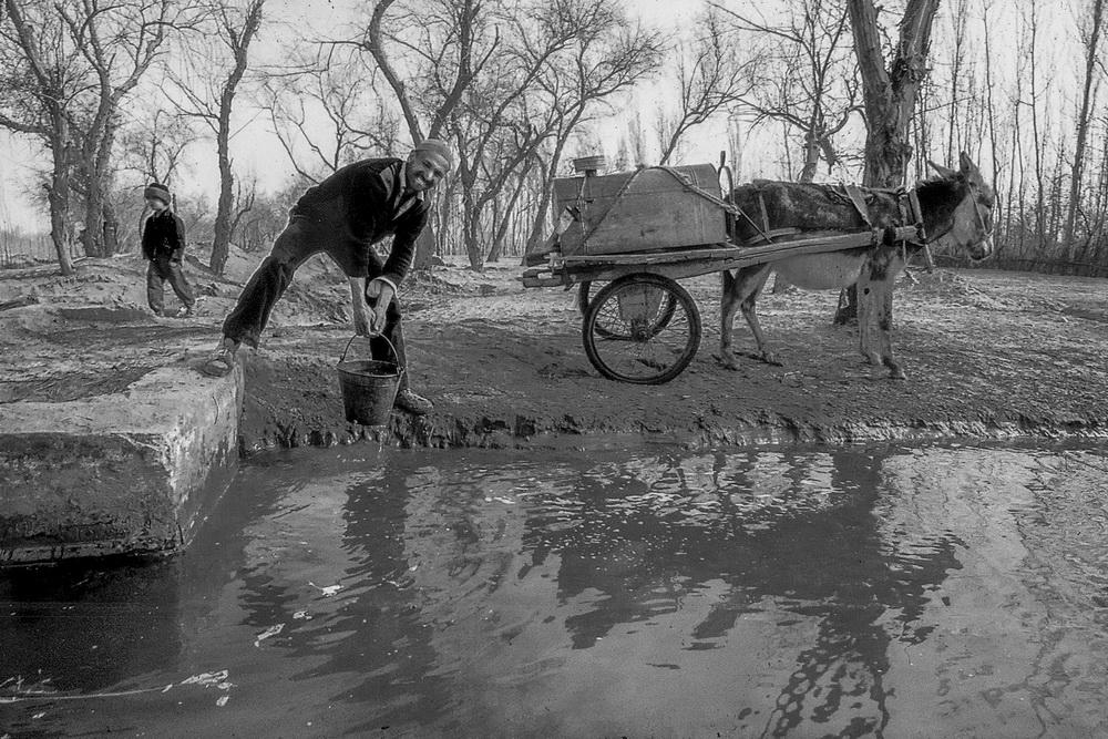 上个世纪90年代,新疆和田地区策勒县一位农民在一处涝坝边取水(资料照片)。新华社记者 沈桥 摄