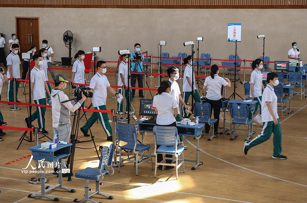 7月2日,海南华侨中学高中部高考模拟演练现场,考生戴着口罩有序经过测温区。