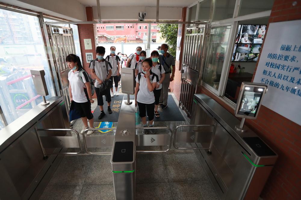 8月10日,在位于武汉的湖北省水果湖一中,初一、初二年级学生通过测温通道入校。