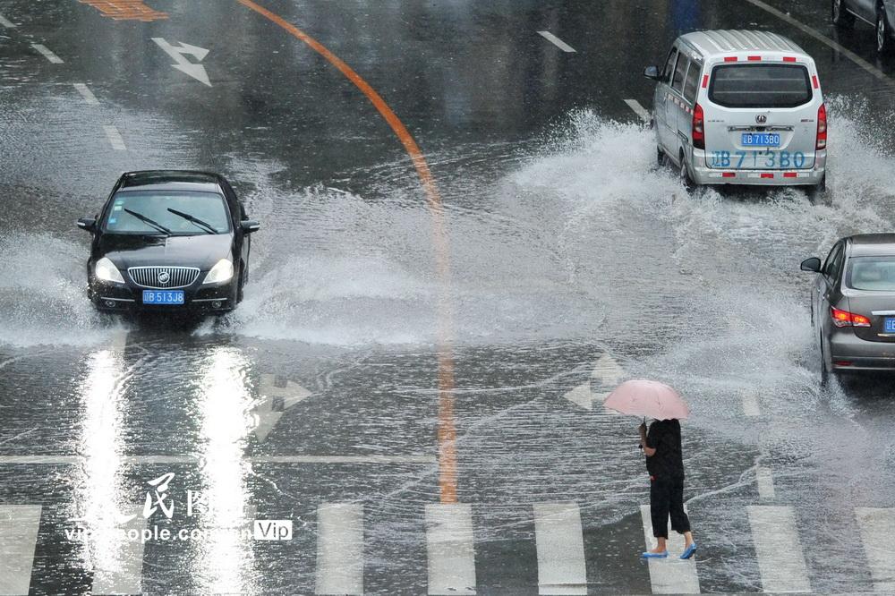 2020年8月13日,人们在大连市甘井子区华泉街冒雨出行。