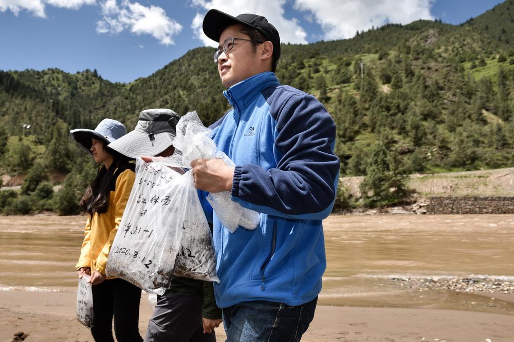 8月12日,长江科学院的科考队员高志扬(右)在位于青海省玉树藏族自治州囊谦县的江西林场完成采样后返回。