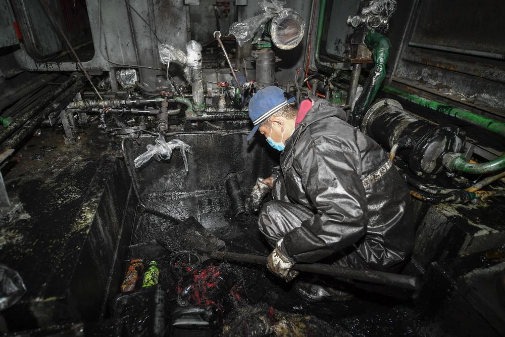 张洪波在清洗前清理动力室内的垃圾、杂物(8月17日摄)。