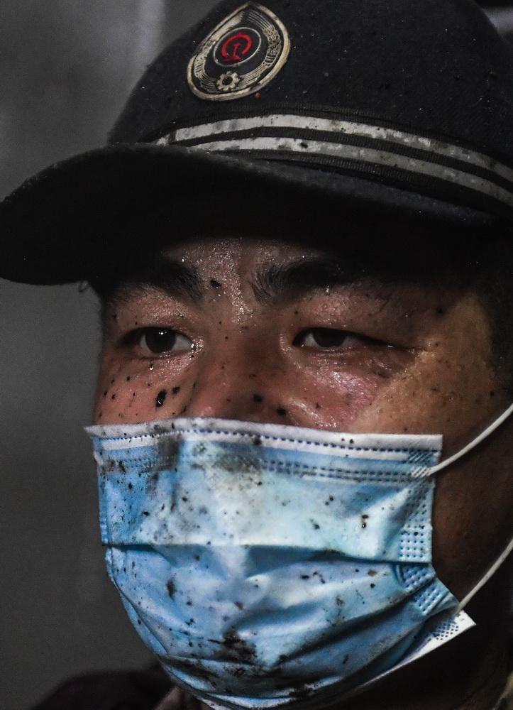 张洪波在动力室内进行清洗保养作业时,油污飞溅在他的脸上和口罩上(8月17日摄)。