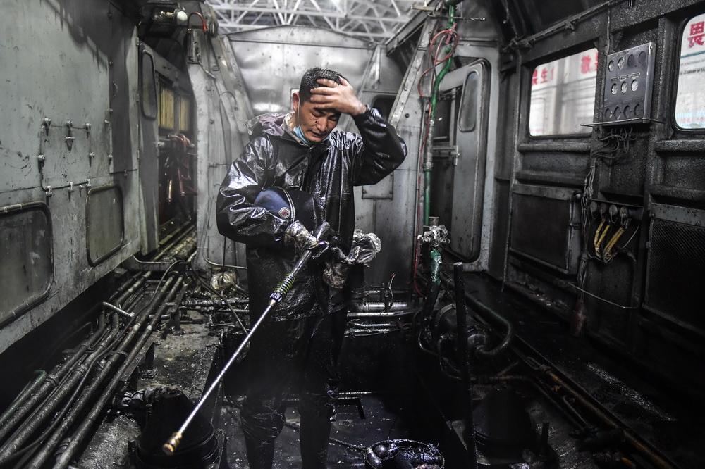 张洪波在清洗保养过程中擦汗休息(8月17日摄)。