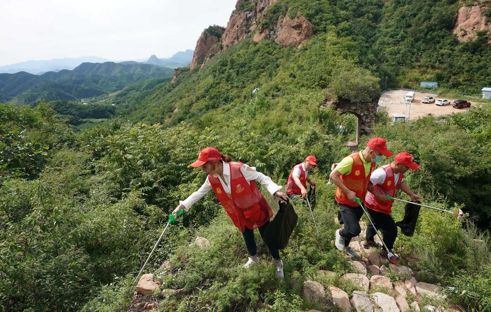 8月20日,秦皇岛阳光义工公益服务中心的志愿者在正冠岭长城捡拾垃圾。