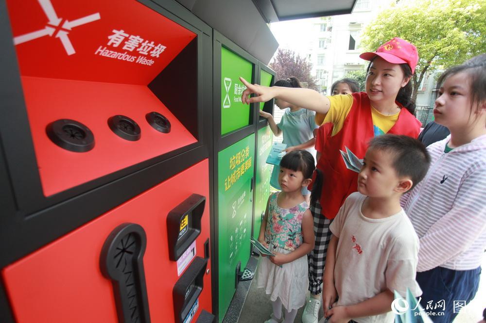 8月27日,在江苏省扬州市汤汪乡杉湾花园社区,志愿者为小朋友讲解垃圾分类知识。