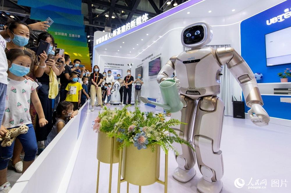 参观者围观智能家居机器人浇花。(人民网记者 翁奇羽 摄)