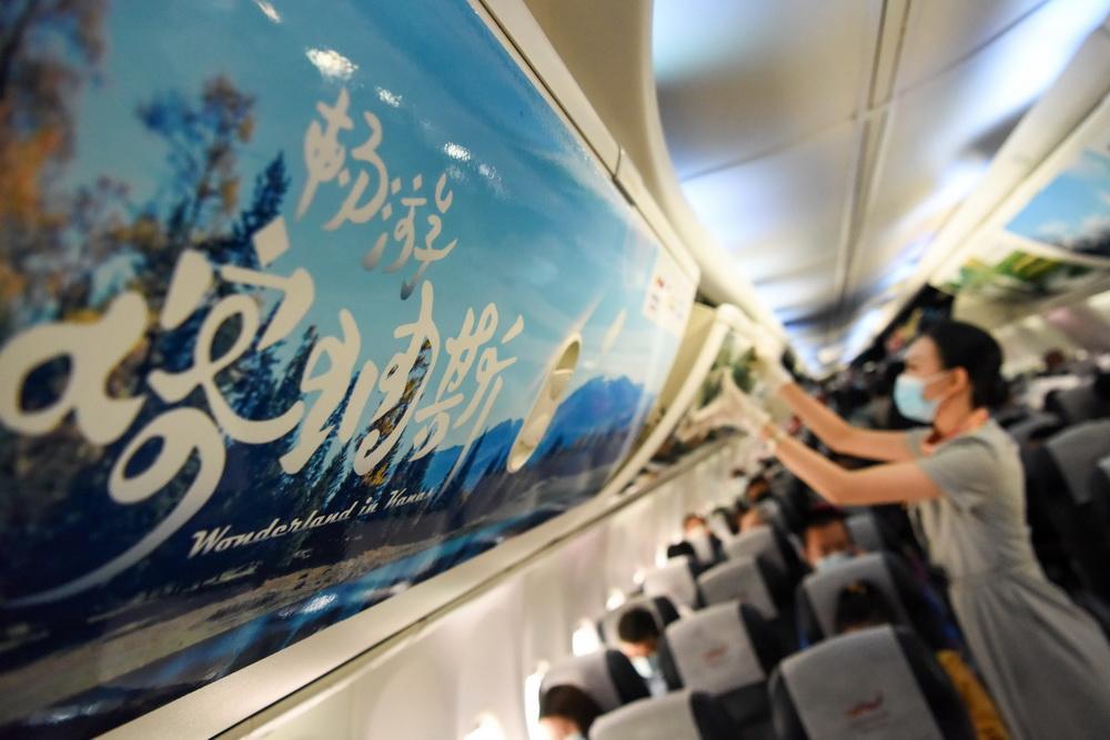 """9月15日,空乘人员为乘坐乌鲁木齐航空""""喀纳斯号""""飞机的旅客服务。"""