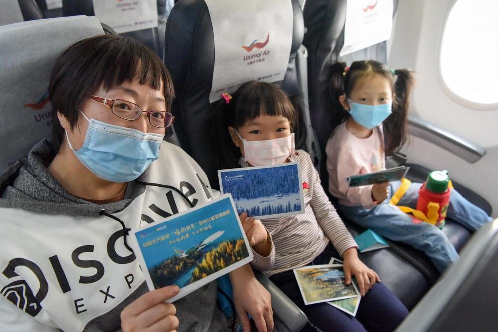 """9月15日,乘坐""""喀纳斯号""""的旅客展示首航纪念明信片。"""