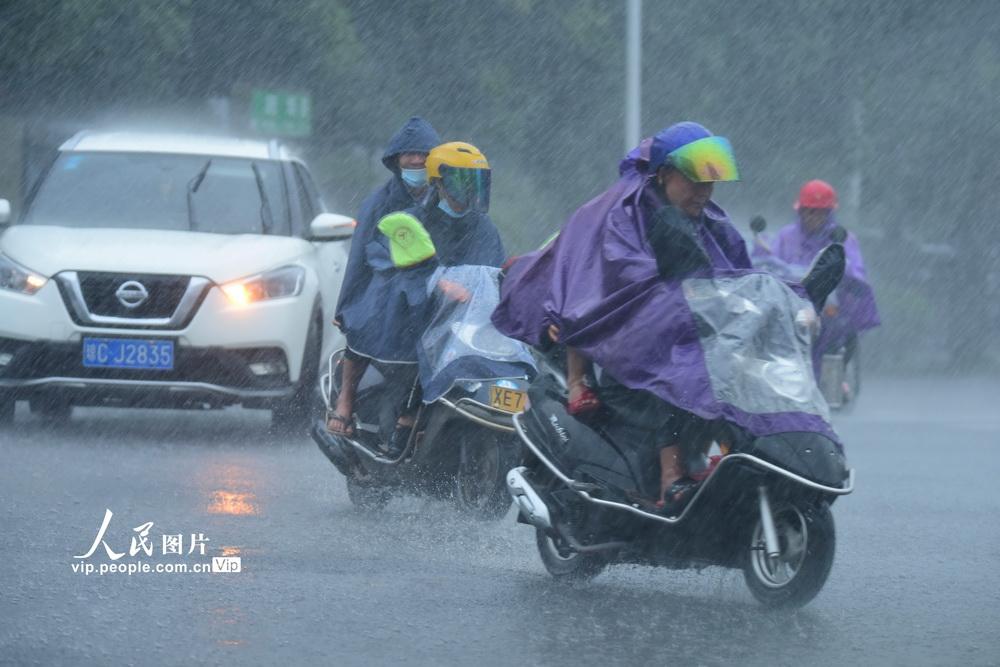 2020年9月18日,海南琼海,市民在暴雨中出行。