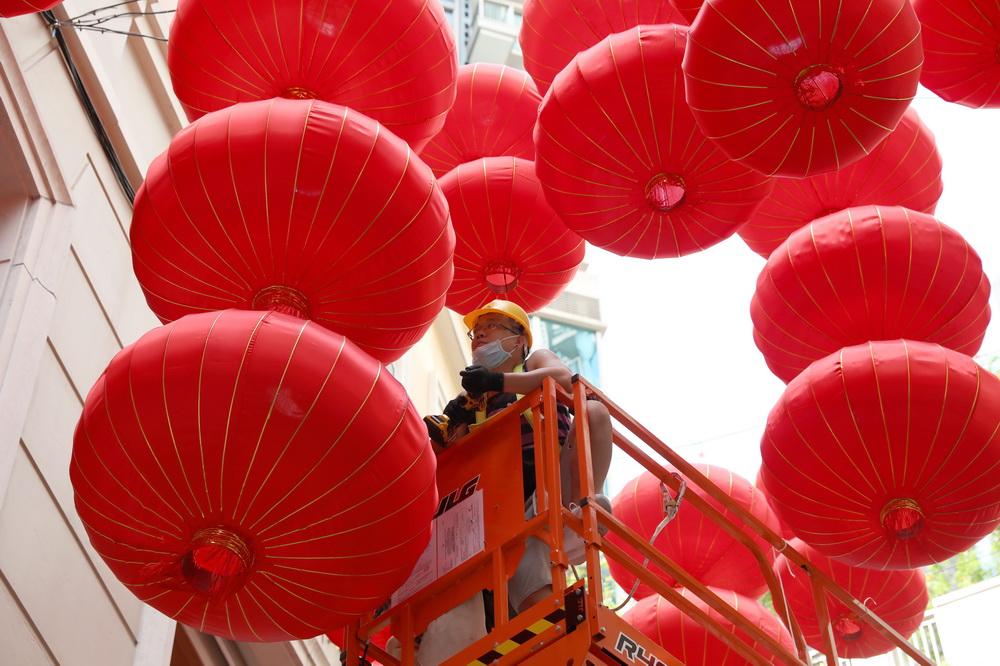 9月22日,工人在香港利东街上悬挂灯笼。