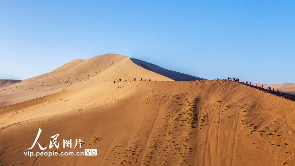 2020年10月7日,在甘肃省酒泉地区敦煌市鸣沙山月牙泉风景区,游客们游览月牙泉风光。