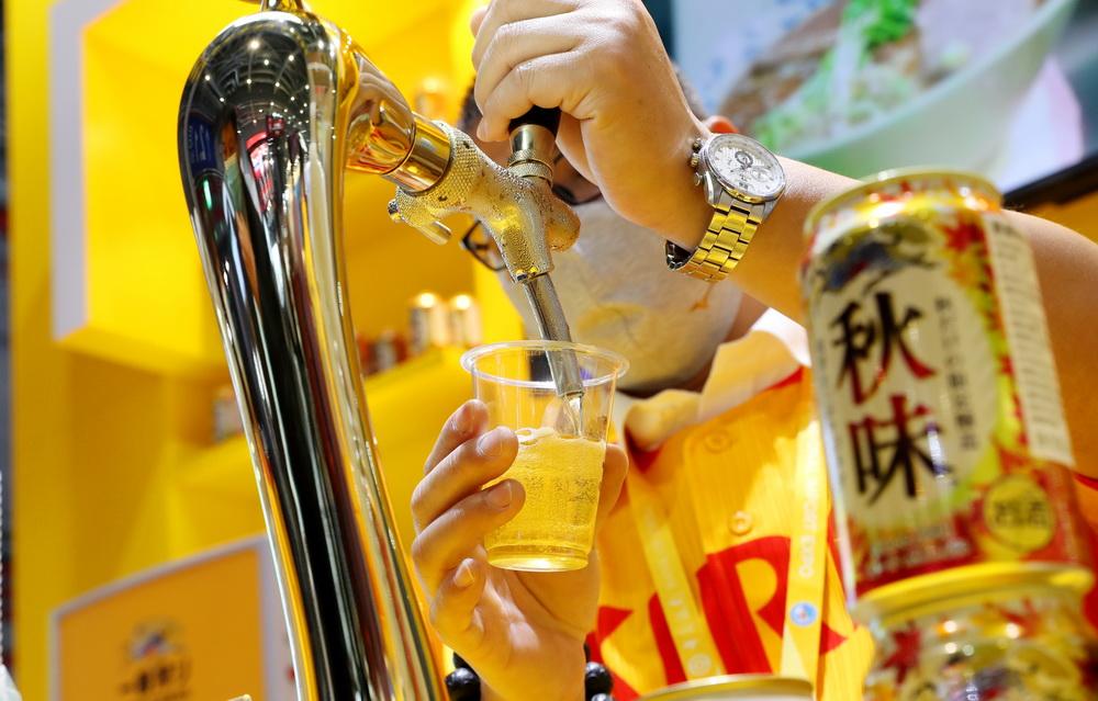 11月7日,工作人员在进博会食品及农产品展区麒麟啤酒展台上倒啤酒。新华社记者 方喆 摄