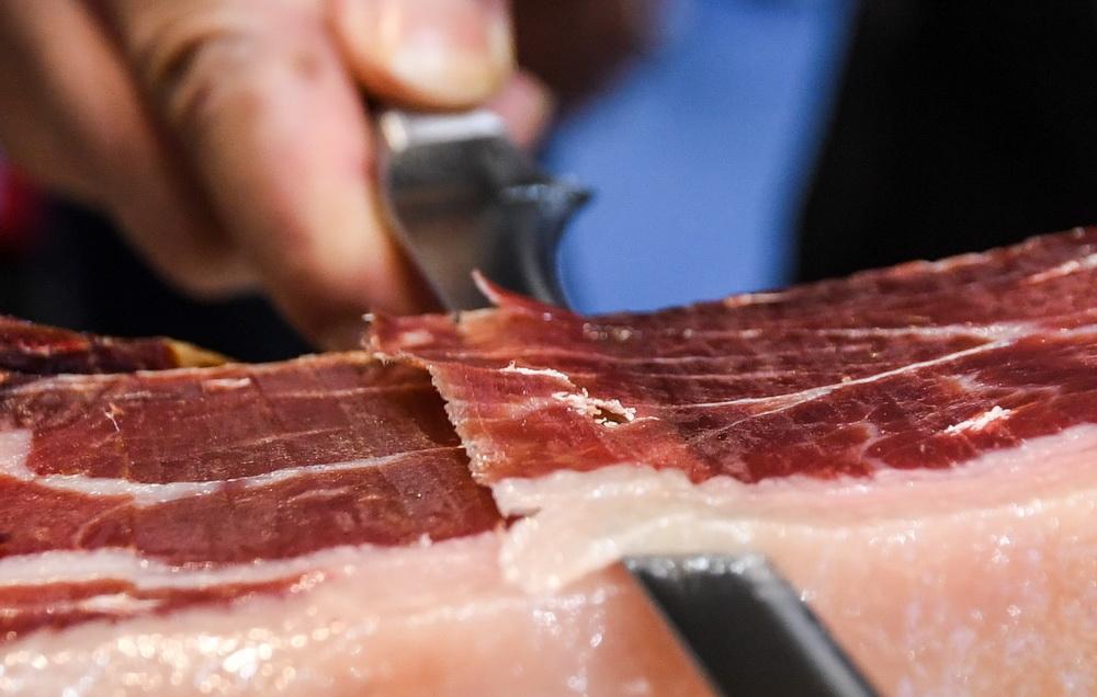 11月6日,在进博会食品及农产品展区,一展台的工作人员在切火腿片。新华社记者 陈晔华 摄