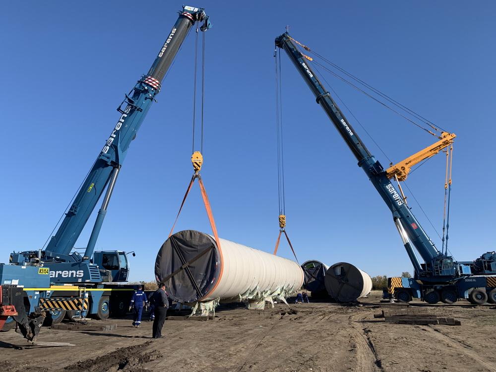 在哈萨克斯坦科斯塔奈州风电场施工现场,工作人员吊装中国生产的风机叶片(10月30日摄)。新华社发(寰泰能源供图)