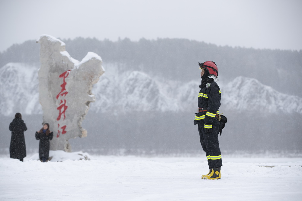 11月7日,在漠河市北极村,消防员郑树君在雪中执勤。