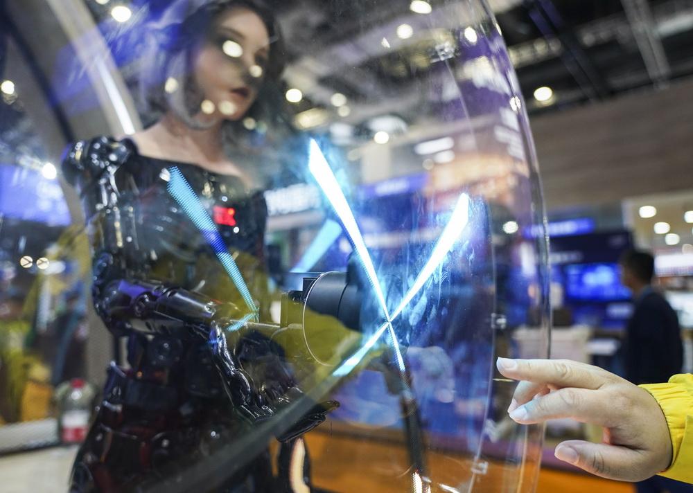 11月9日,观众在技术装备展区微软展台参观EX仿生机器人,人手与机械手隔空相对。