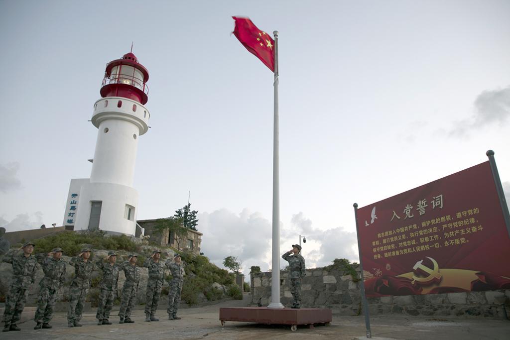 在江苏省灌云县开山岛,王仕花(右一)与轮值民兵举行升国旗仪式(9月27日摄)。 新华社记者 刘芳 摄