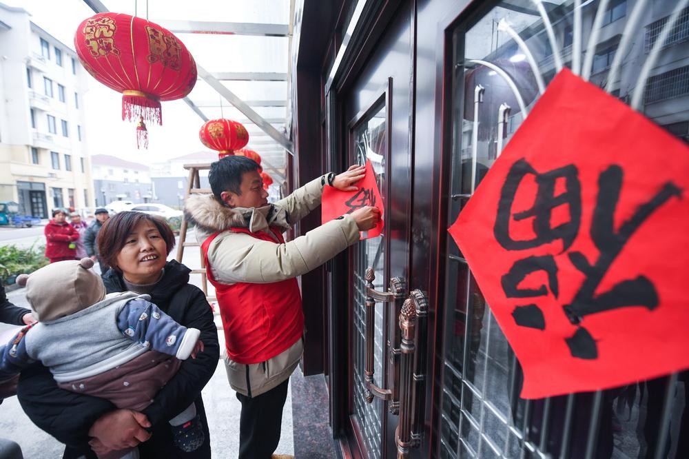 1月5日,东林镇星华村的党员志愿者在新农村新居给村民贴福字。