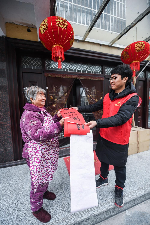 1月5日,东林镇星华村的党员志愿者在新农村新居给村民送春联。