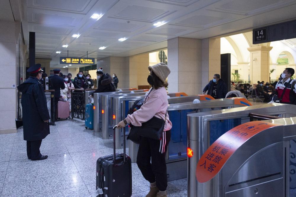 2021年1月6日,在哈尔滨站,旅客通过闸机准备上车。