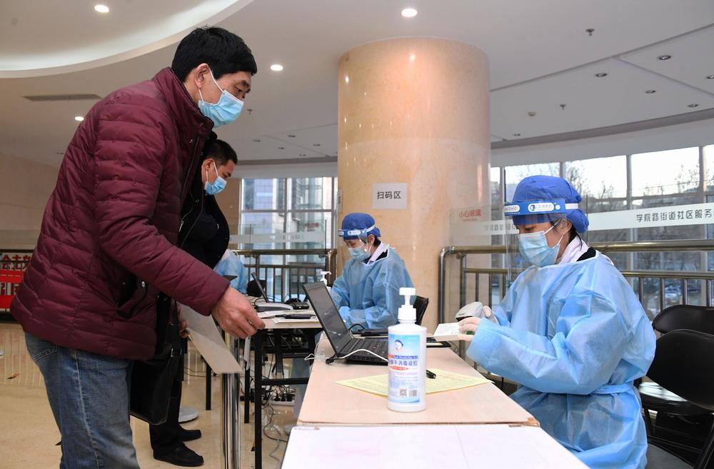 1月11日,在北京市海淀区学院路街道的一处临时新冠疫苗接种点,医务人员(前右)扫描新冠疫苗电子监管码,准备接种工作。新华社记者 任超 摄