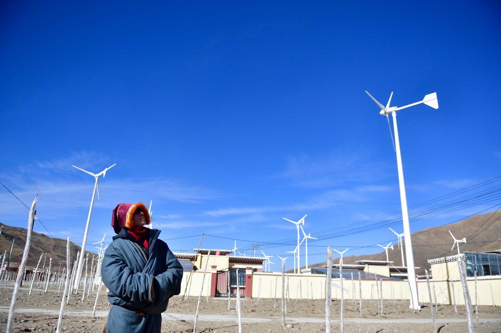 1月11日,隆亚村村支部书记贡保多杰在查看搬迁点的风力发电机组运行情况。