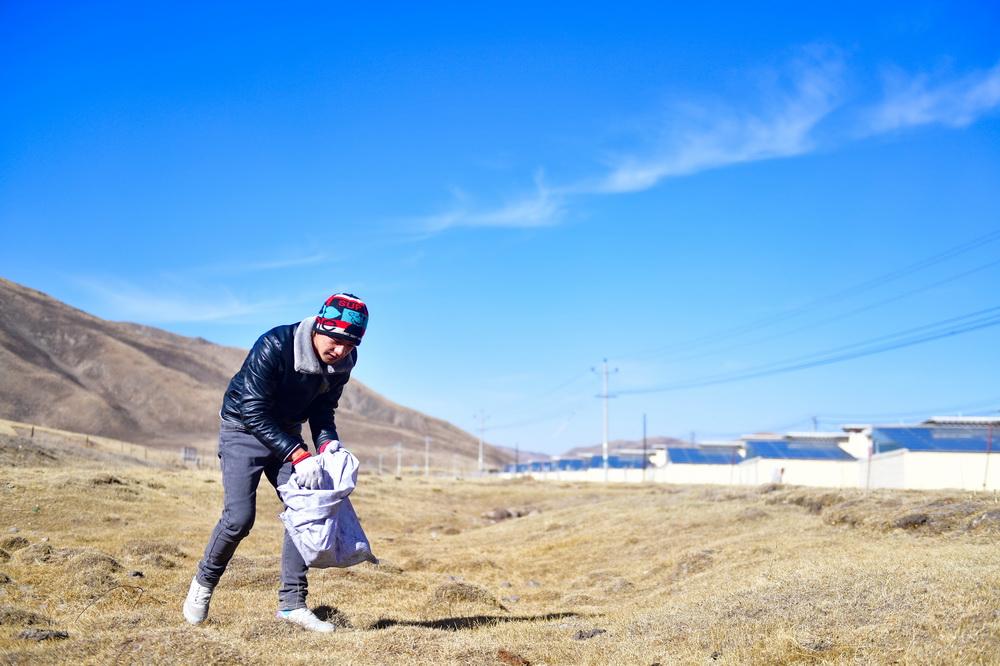 1月11日,隆亚村牧民东保在搬迁点周边的草原上捡拾垃圾。