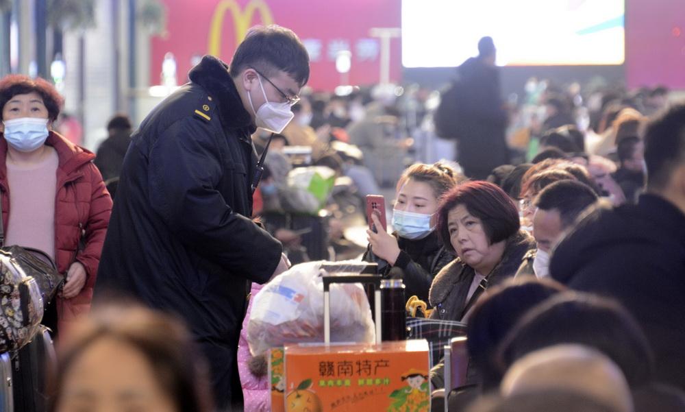 1月12日,北京站工作人员在候车室进行防疫巡查,提示用餐后的旅客及时佩戴口罩。