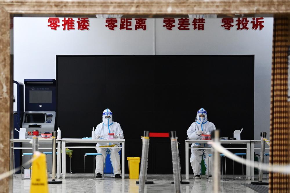 1月23日,医务人员在哈尔滨市抚顺社区核酸检测点值守。新华社记者 王建威 摄