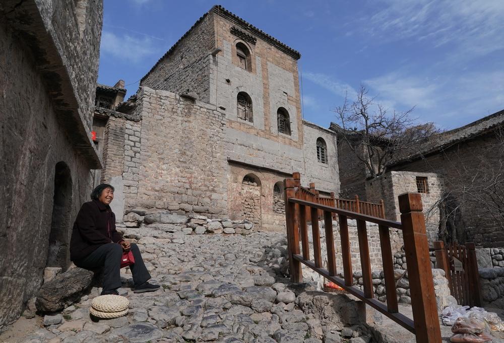 2月21日,在井陉县南障城镇大梁江村,一位老人在街旁休息。