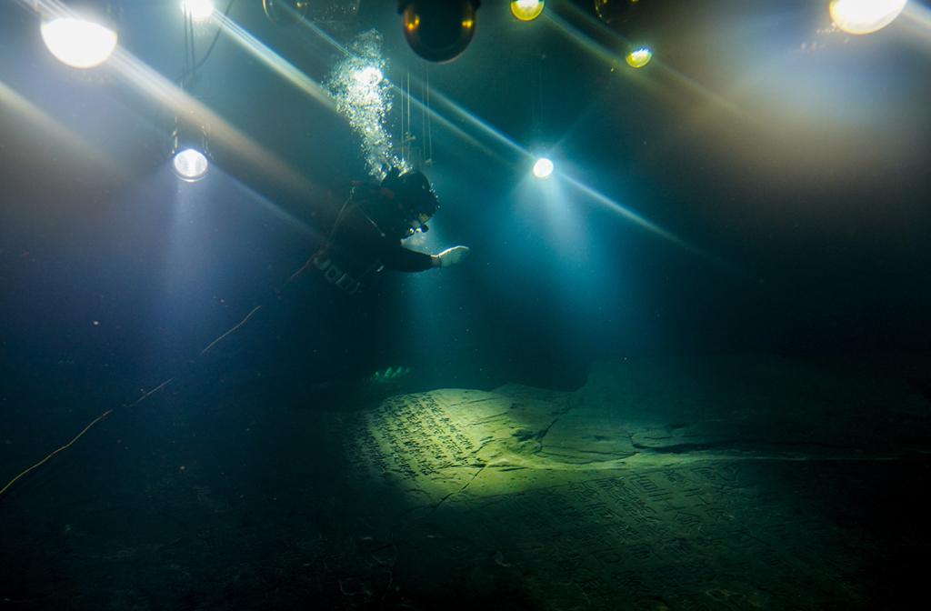 3月15日,在长江水下40多米的白鹤梁题刻无压容器罩内,潜水员在进行清理作业。新华社记者 刘潺 摄