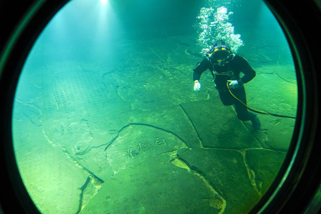 3月15日,在长江水下40多米的白鹤梁题刻无压容器罩内,潜水员在进行清理作业。新华社记者 王全超 摄