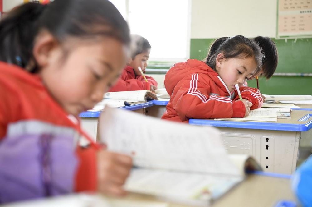 宁夏固原市西吉县马建乡大坪小学一年级学生铁嘉欣(右二)在课堂上写字(3月15日摄)。新华社记者 冯开华 摄