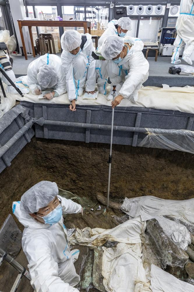 """在三星堆遗址考古发掘现场3号""""祭祀坑"""",考古人员用全站仪为新发现的文物定位(3月10日摄)。新华社记者 沈伯韩 摄"""