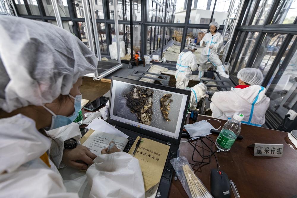 在三星堆遗址考古发掘现场,考古人员利用电脑现场查看新发现的象牙雕,并进行记录(3月10日摄)。新华社记者 沈伯韩 摄